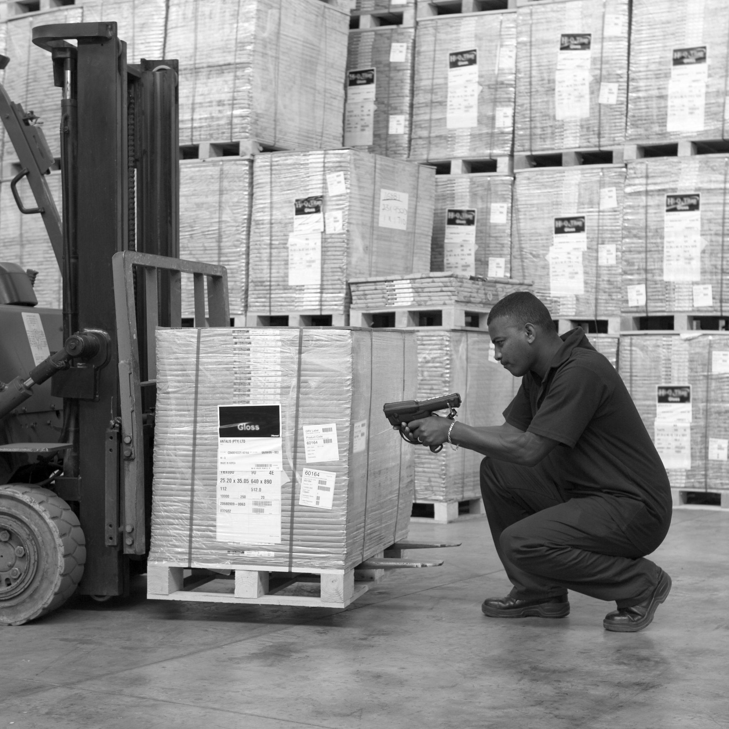 Man scanning pallet in warehouse