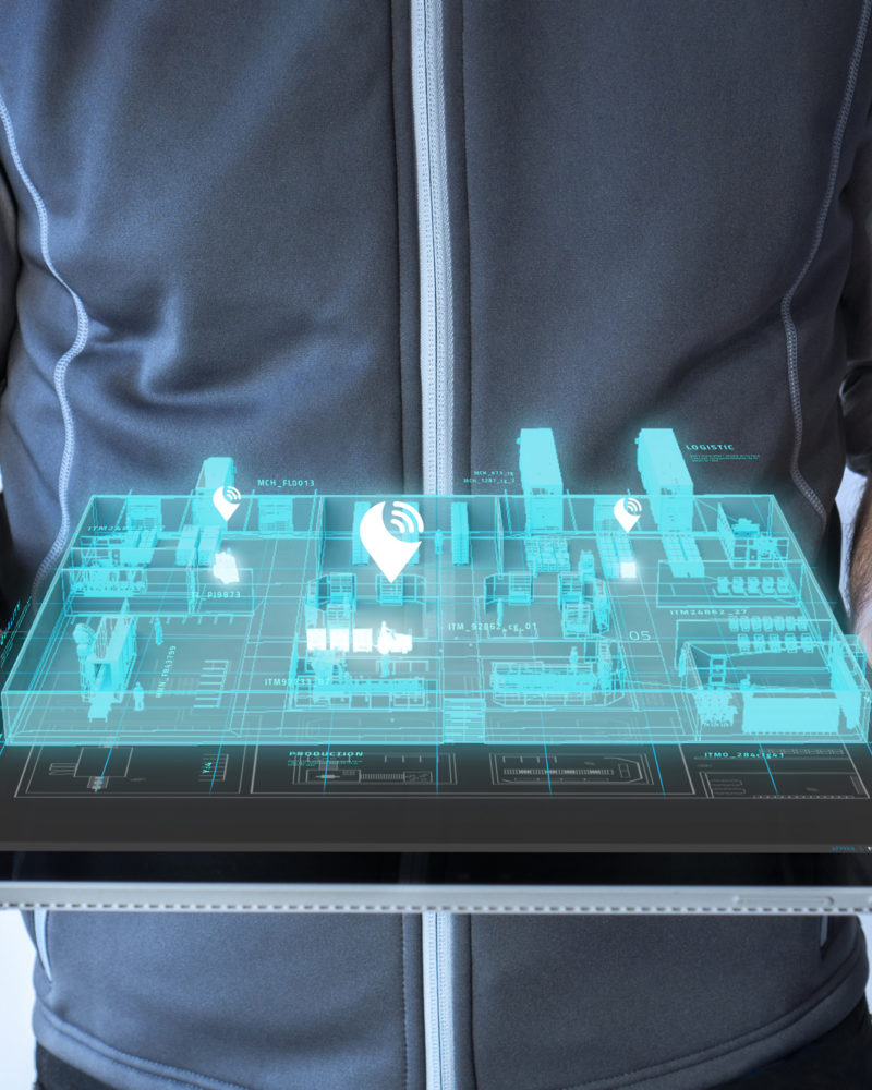 Businessman with a tablet in hand and a digital factory hologram