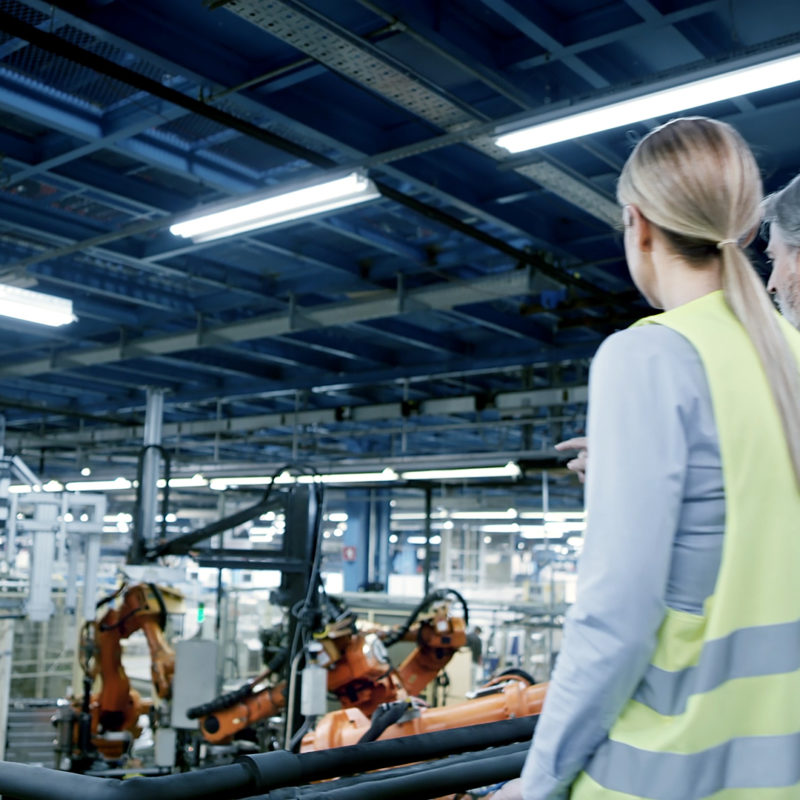 Two factory workers walking in the shopfloor.