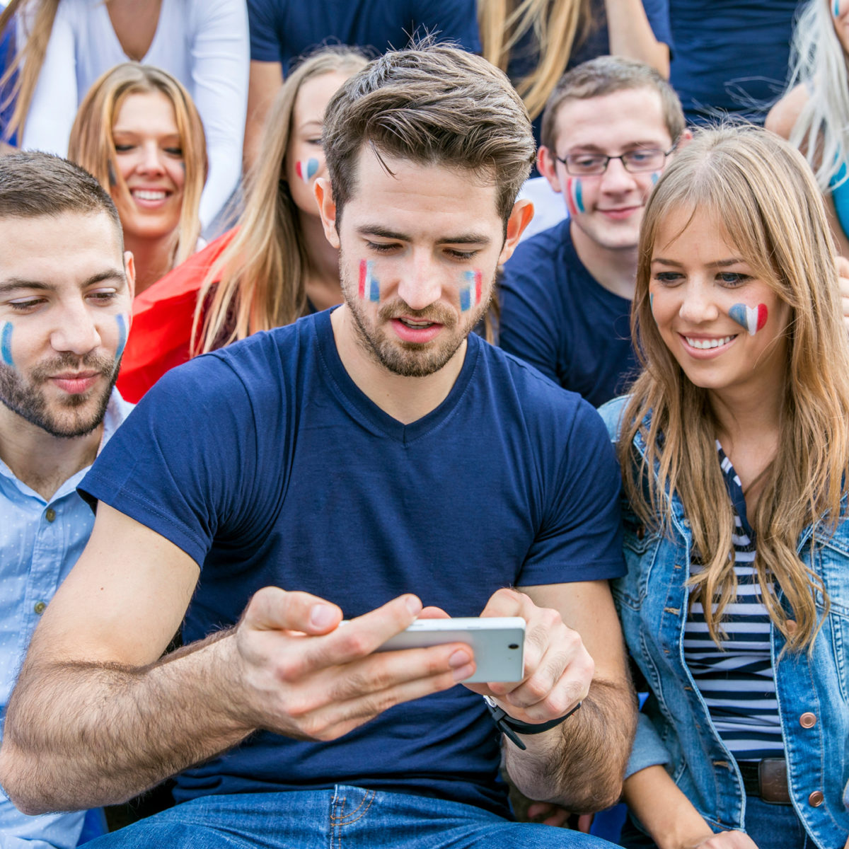 Group of soccer fans text messaging