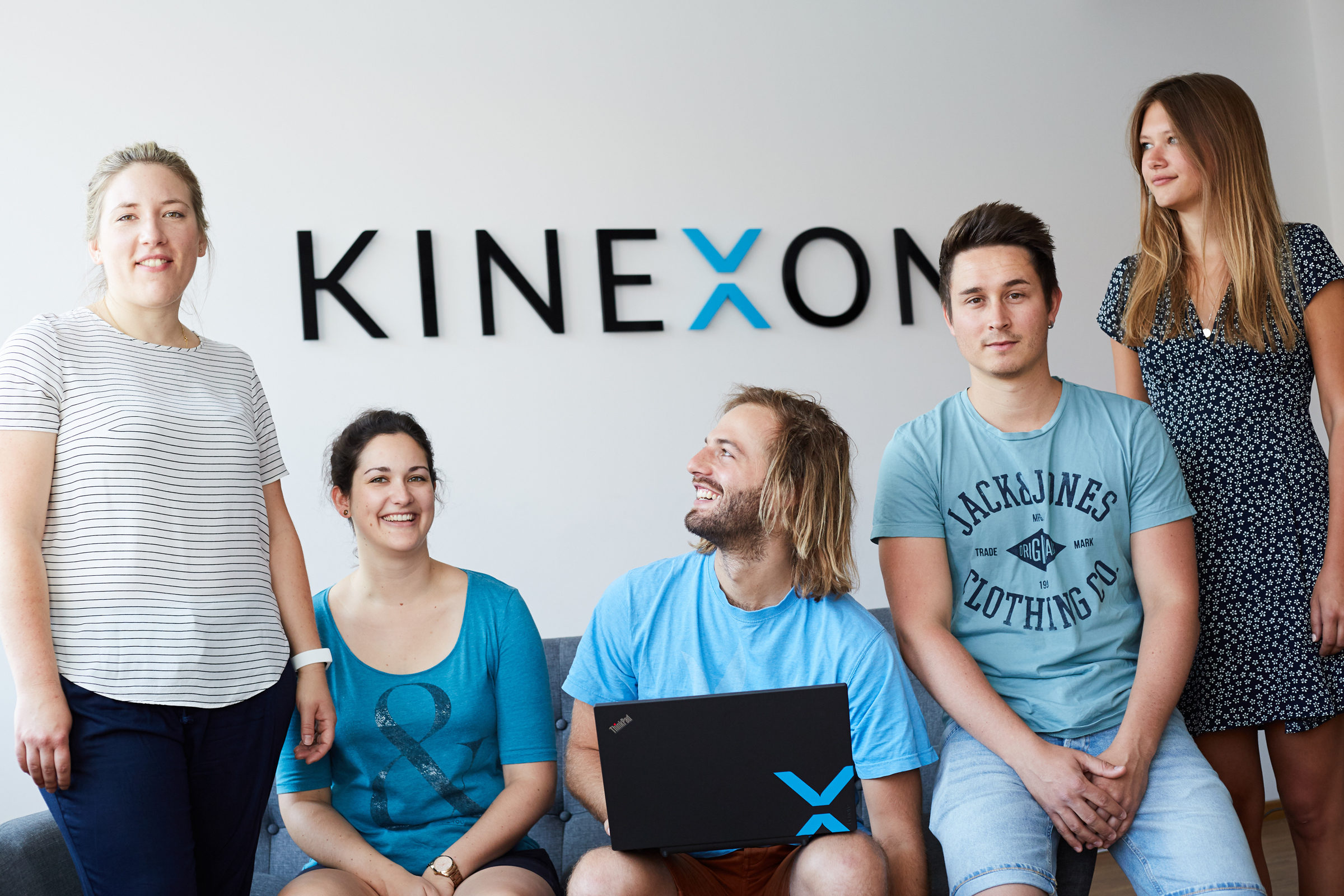 Employees in front of the KINEXON wall