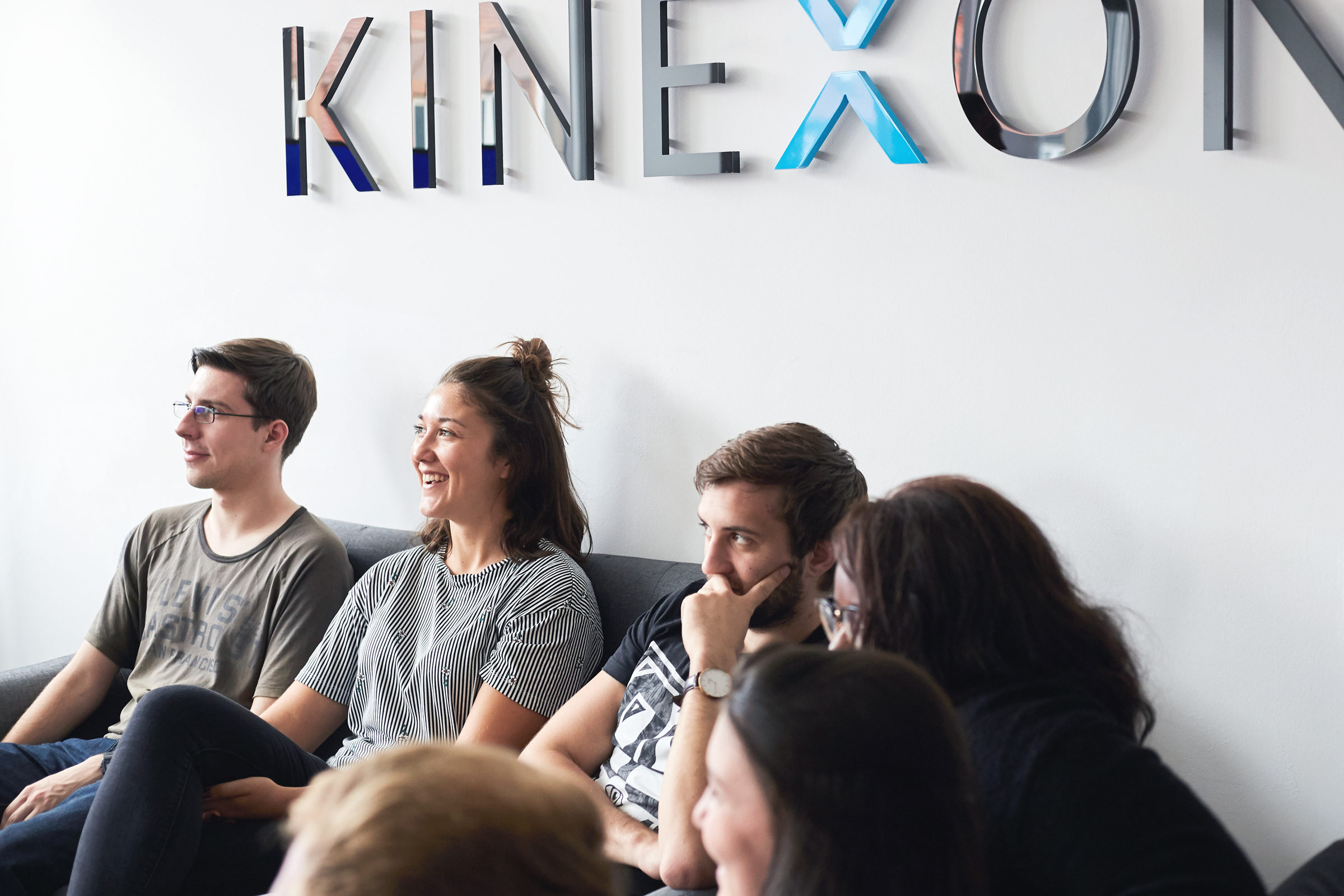 Employees sitting on the couch in front of the KINEXON logo