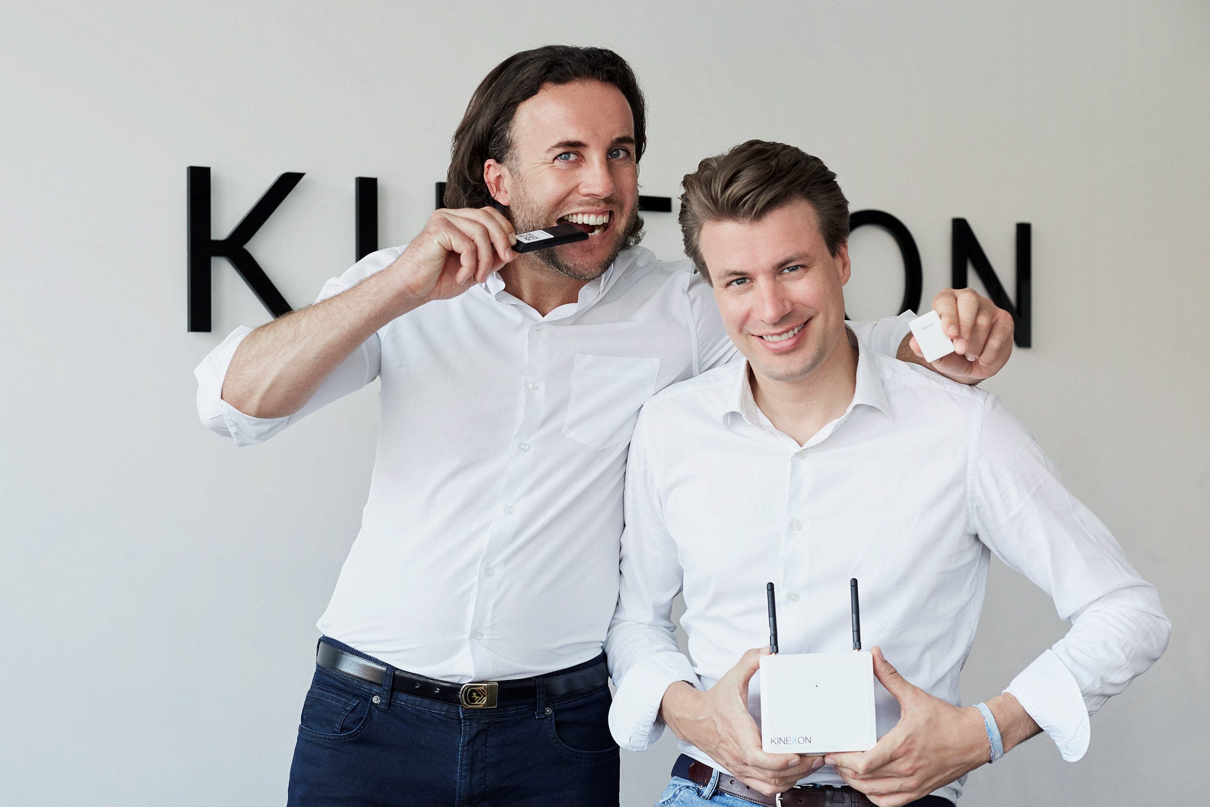 Alexander Huettenbrink and Oliver Trinchera with the anchor in front of the KINEXON logo